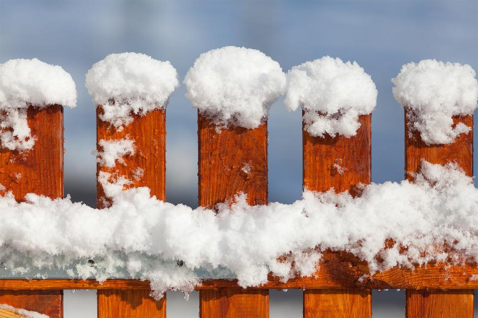 Detail of the top of a fence, covered in snow.