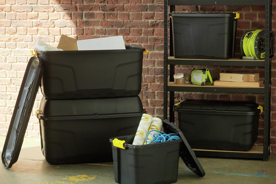 A range of different sized black storage boxes with lids.