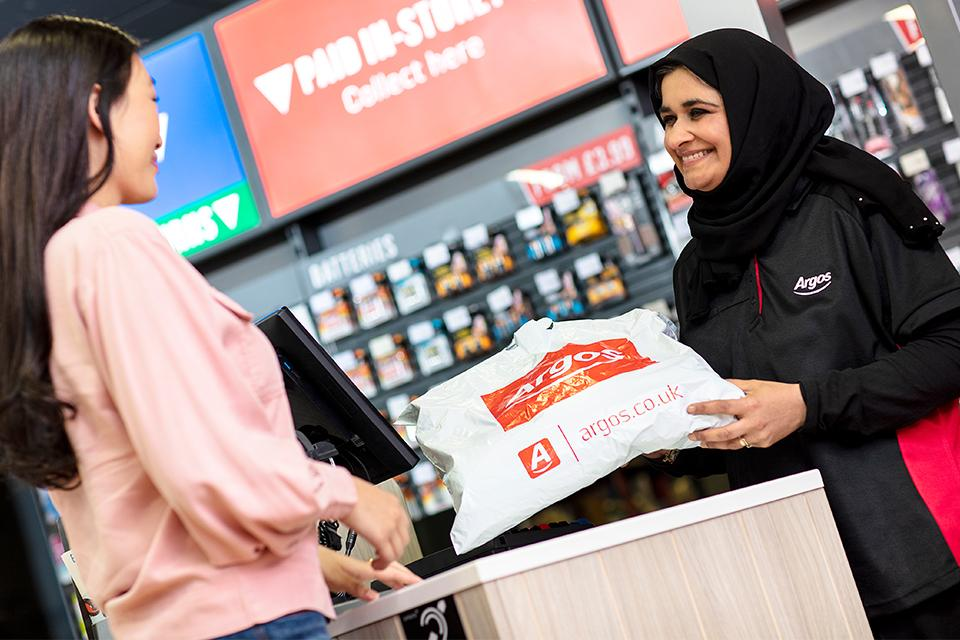 A woman returning an Argos order to a woman at an Argos counter.