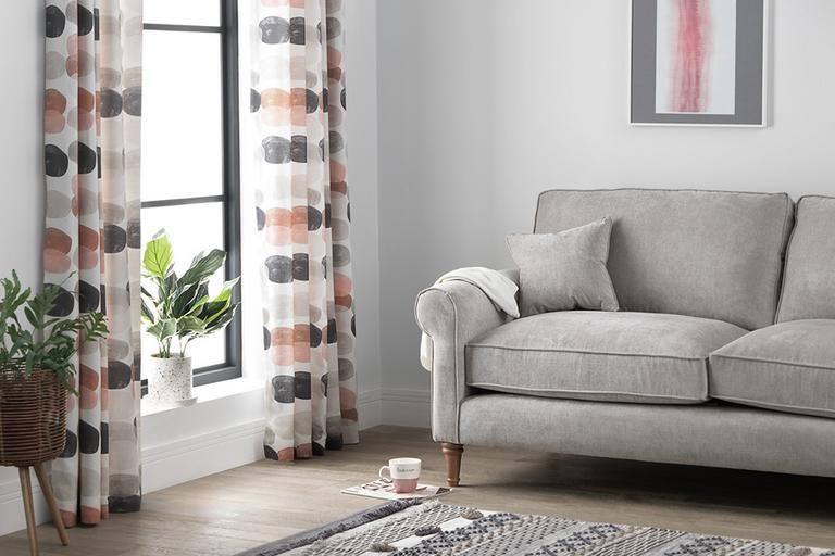 Living room with grey sofa and pink and grey spotted curtains.