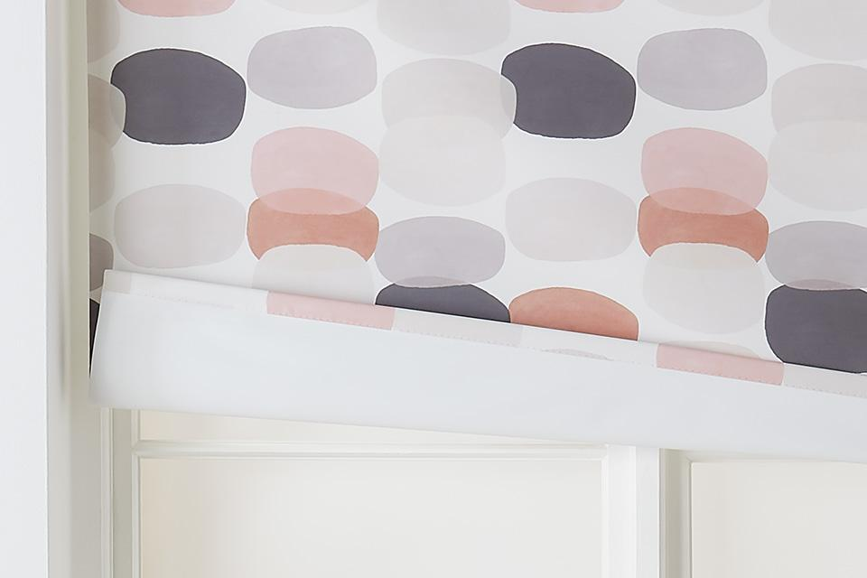 Blackout blinds with a pink and grey pattern.