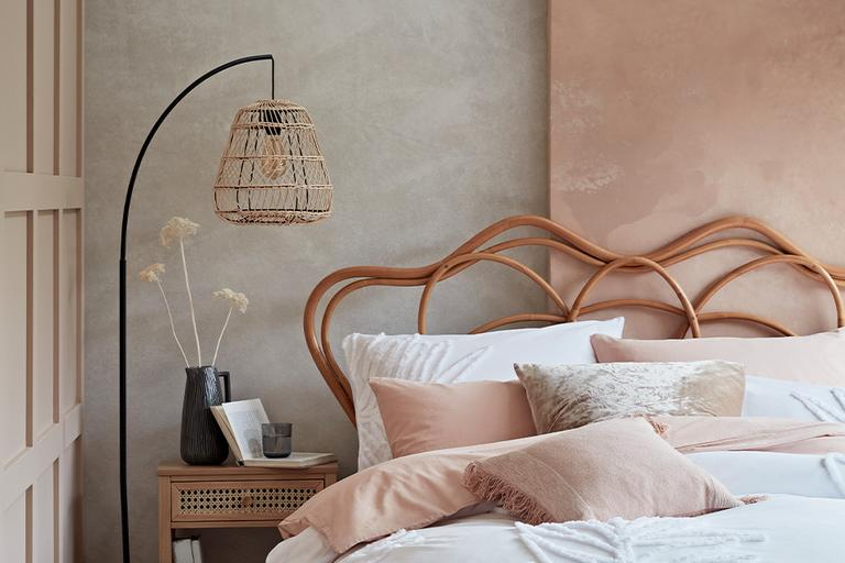 Bedroom with rattan bed frame and white and pink bedding.
