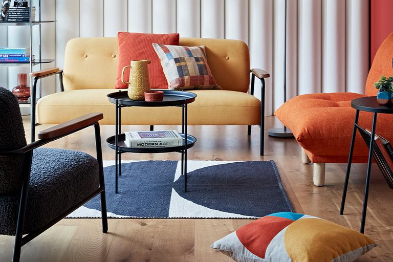 Mid century style living with yellow sofa and orange armchair.