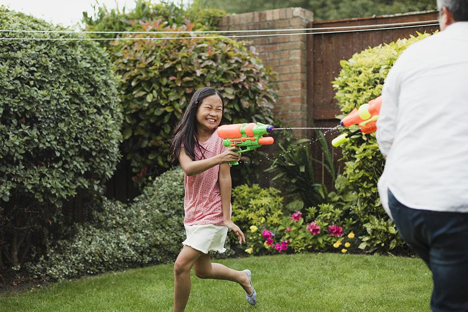 Young girl and her father running around in the garden, shooting each other with water pistols.