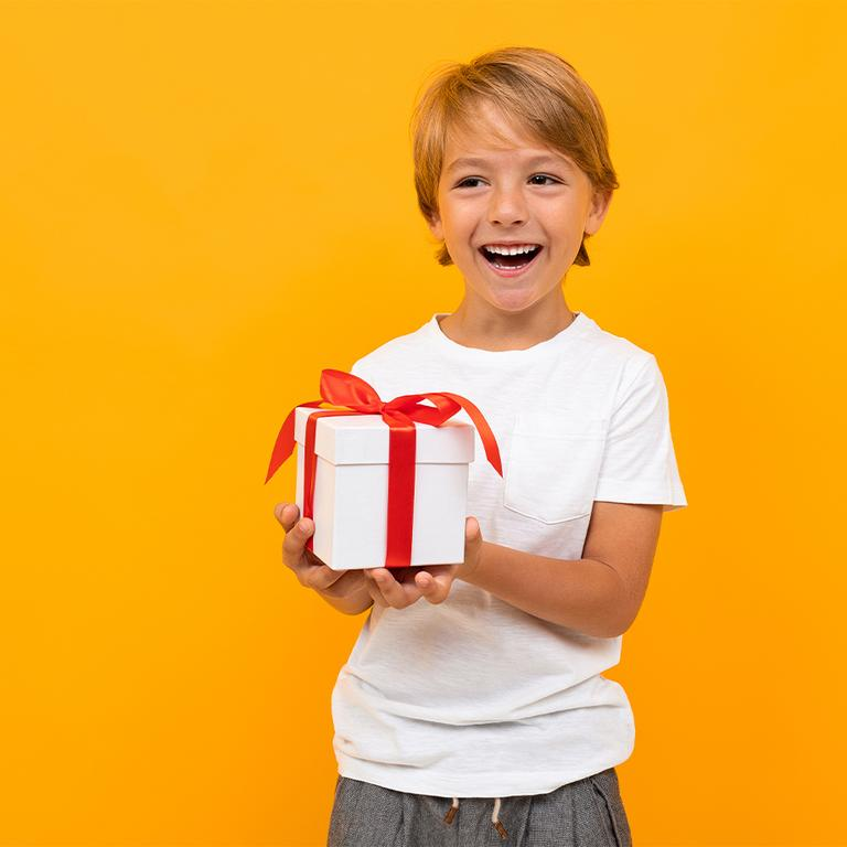 Child smiling, holding a wrapped present.