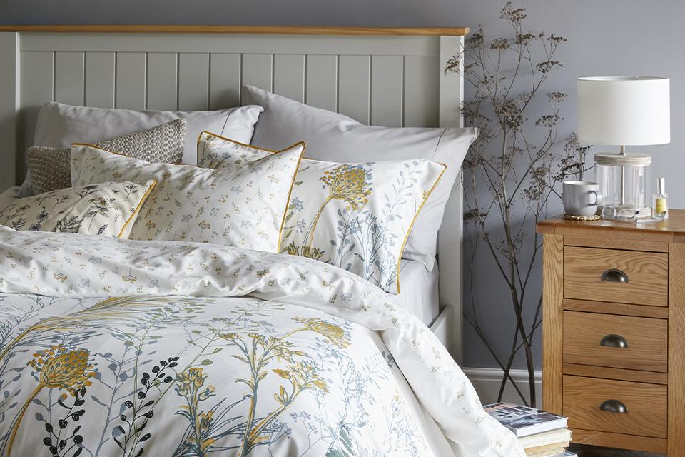 A wooden bed frame covered with delicate floral sheets and lots of comfy pillows.