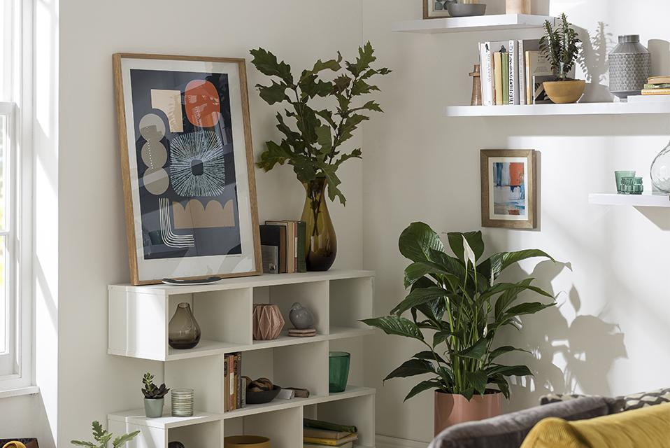 A white cube bookcase in a white living room filled with vases, art, and plant decor.
