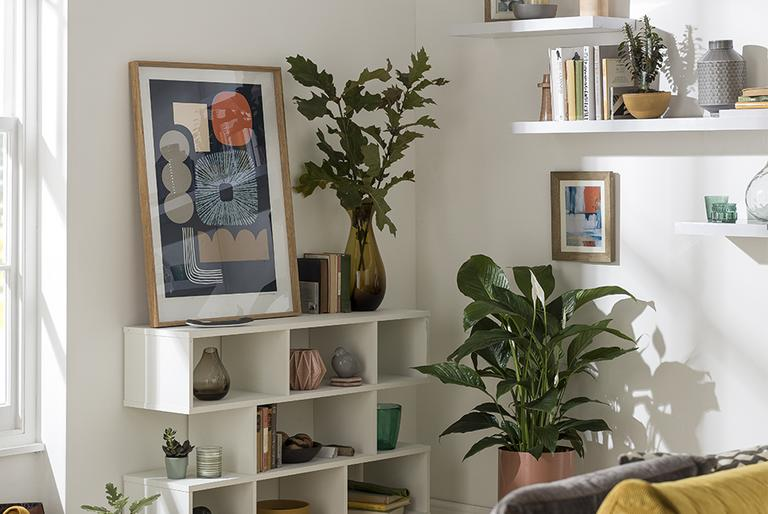 A white living room with a cube style bookcase and lots of plant and gallery decor.