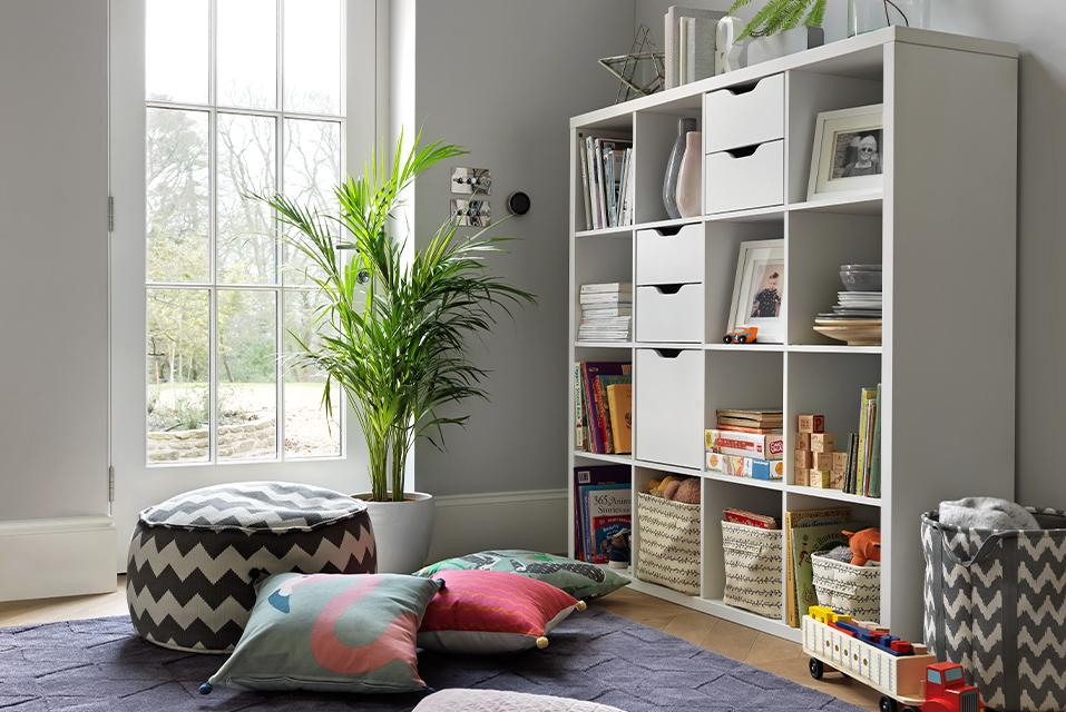 A large, white cube bookcase in a grey living space with lots of floor cushions and storage baskets.