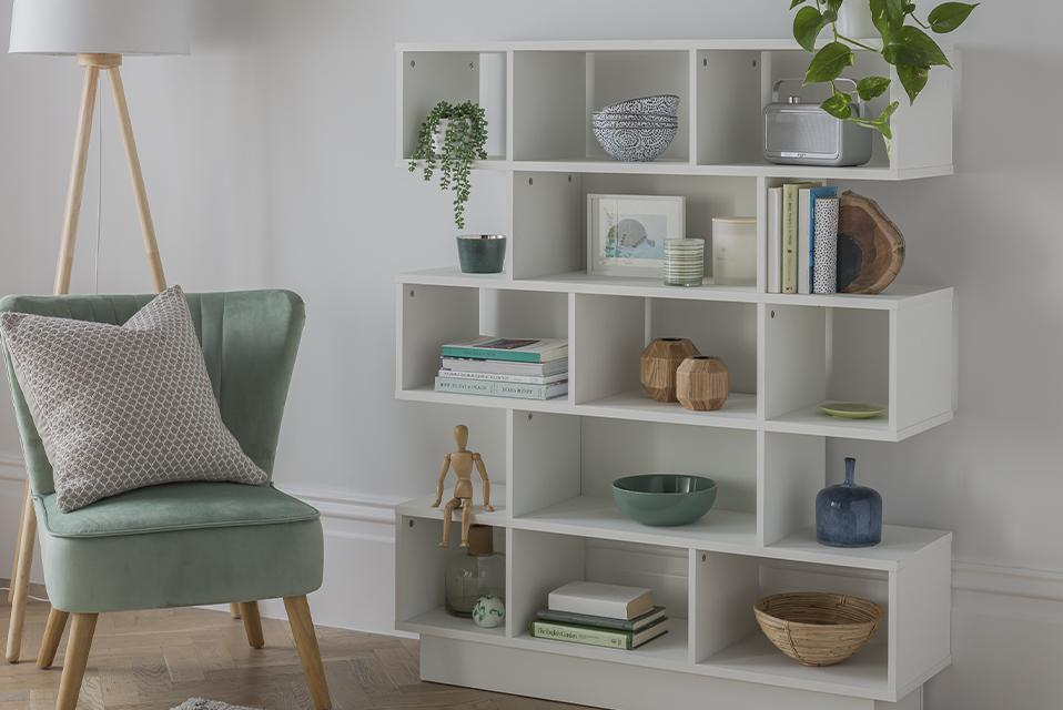 A tiered white cube bookcase beside a duck-egg green accent chair against a white wall.