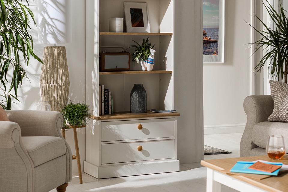 A white and natural wood bookcase unit with both shelves and drawers.