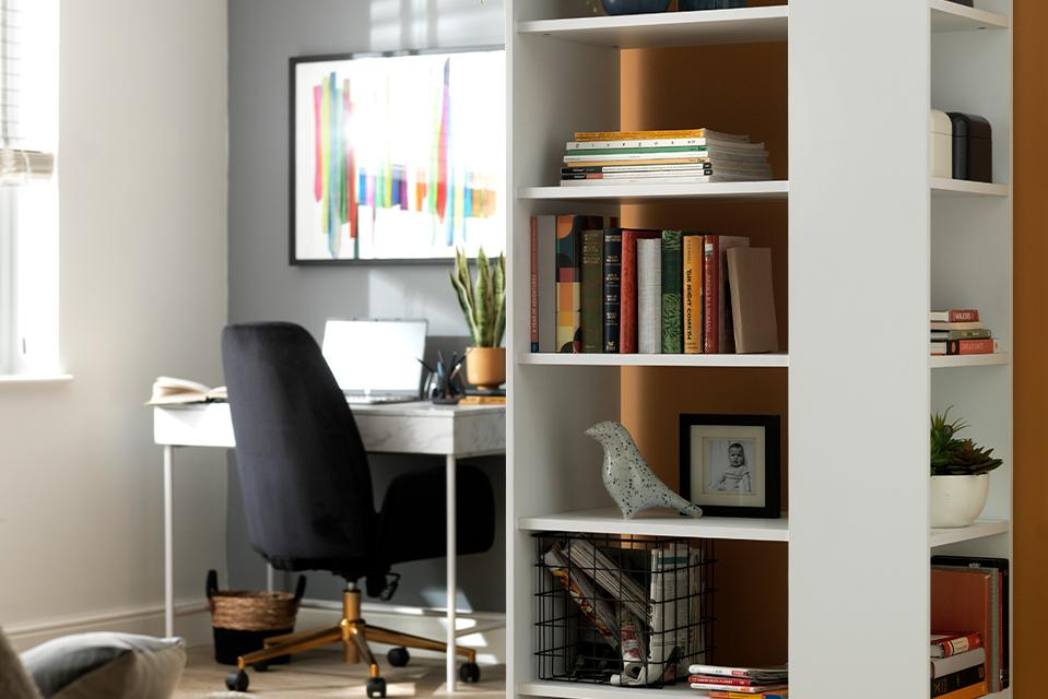 A white bookcase in a grey and orange office space.