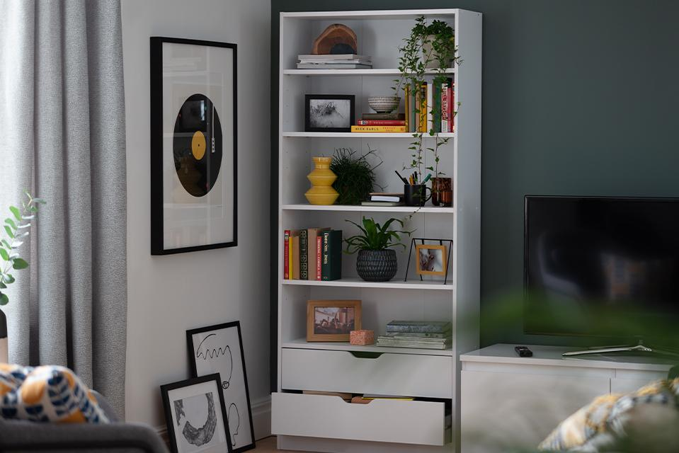 A white bookcase with both shelves and drawers for versatility.
