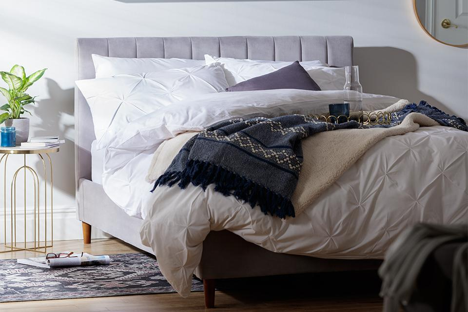 A bed covered in white bed linen and complementary cream and navy throws.