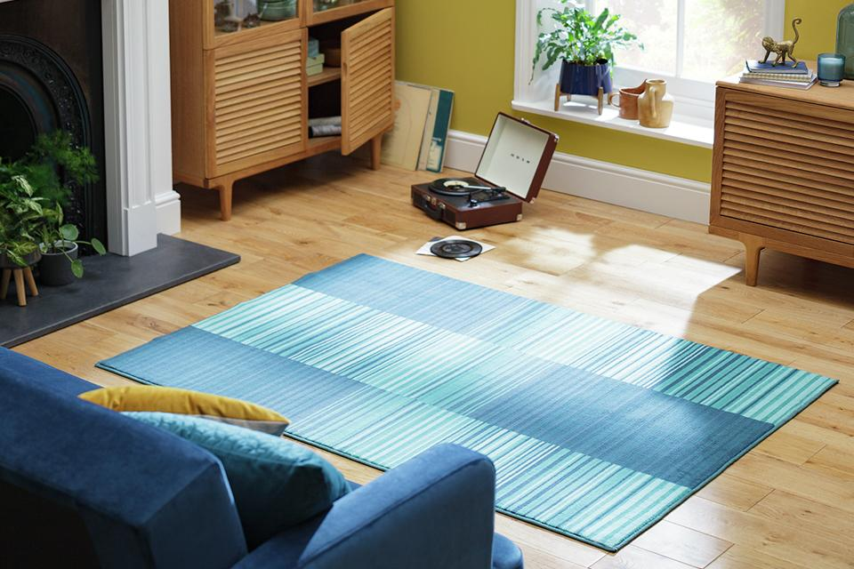 A blue patterned rug on a wooden living room floor.