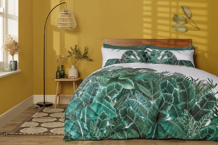 Bedroom setting, with a bold, green leaf design duvet set.