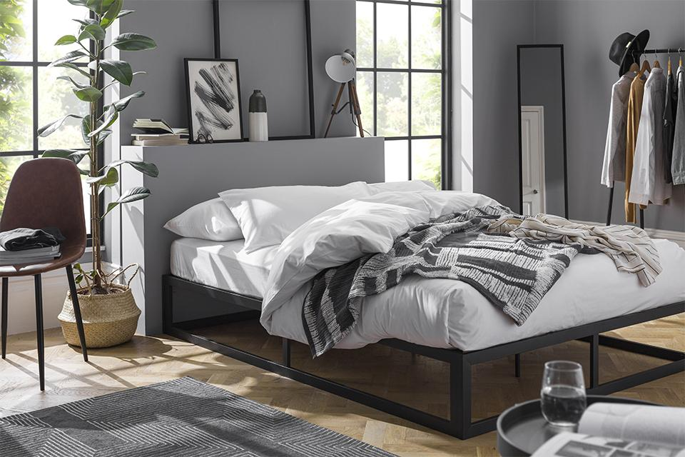 Black metal frame bed with a white duvet set and monochrome throws.