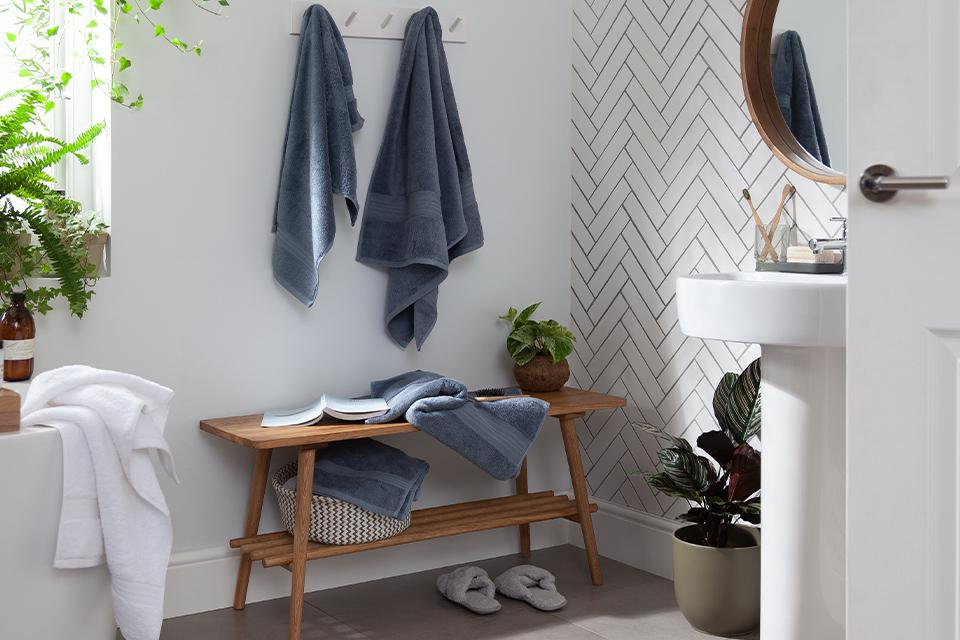 A white bathroom with a wooden bench and blue-grey towels.