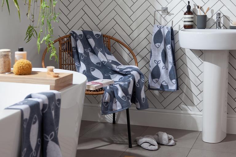 A white herringbone tiled bathroom with two-tone fish print towels laid out on a bamboo chair.