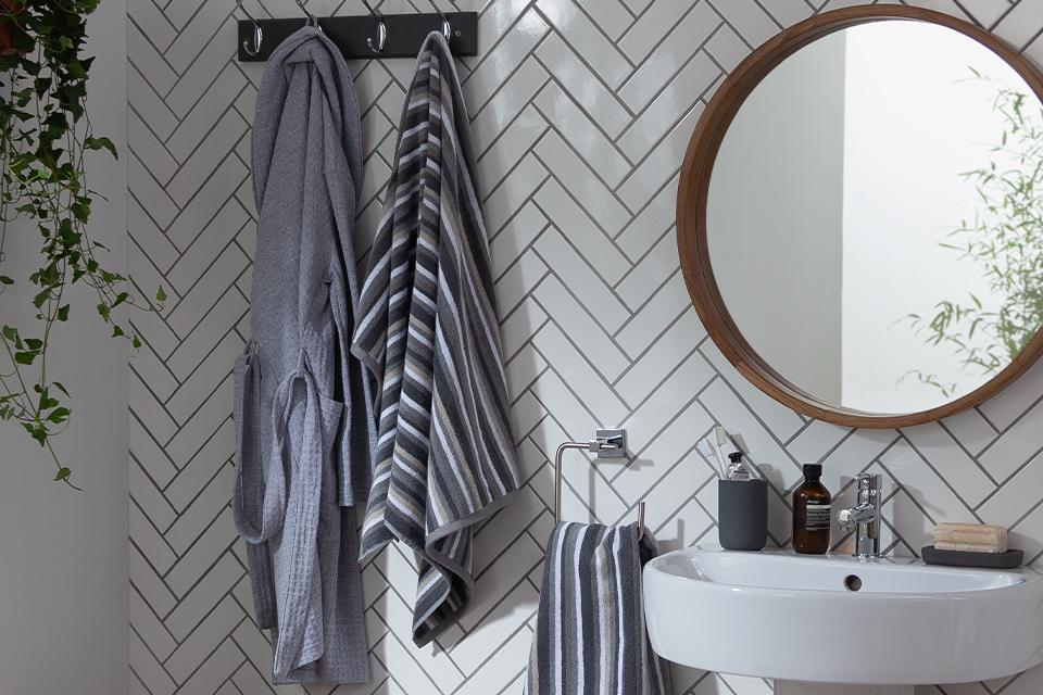 Grey striped towels and a grey bathrobe hung on a white tiled wall.