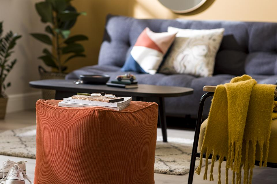 An orange footstool in a living room with boldly coloured accessories.