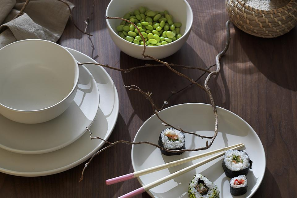 Simplistic cream stoneware on a wooden table with sushi and pastel-tipped chopsticks.