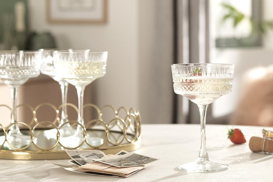 Crystal wine glasses on a mirrored gold tray.