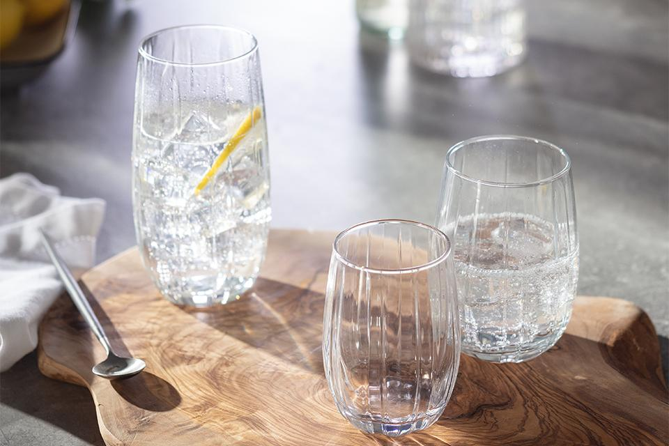 Three etched glasses on a tree slice chopping board.