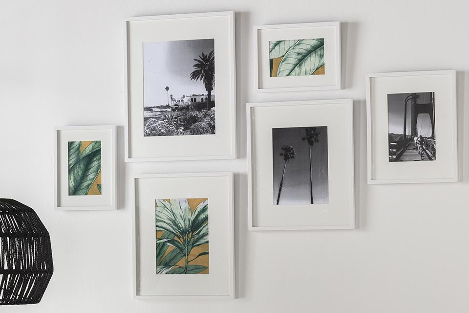 Six different sized art prints in white frames arranged together on a white wall.