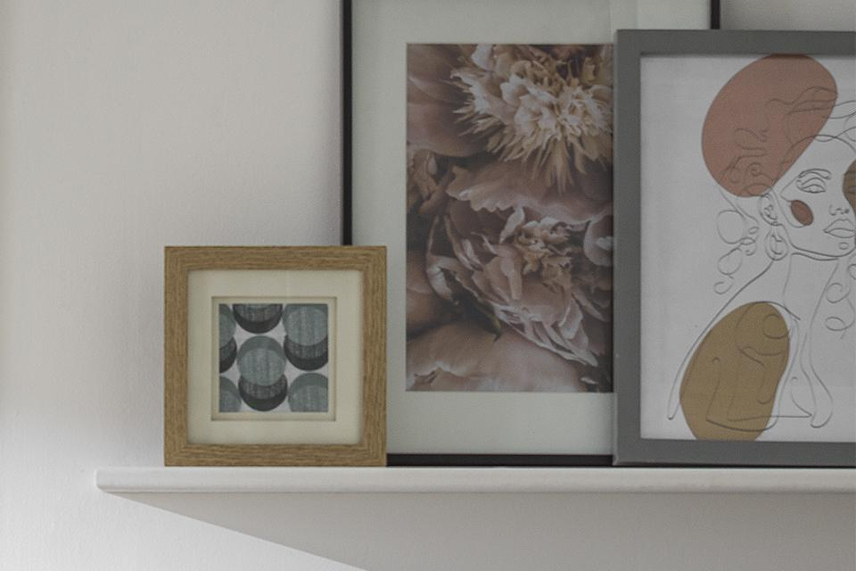 Differently sized art prints in mismatching frames arranged on a floating shelf.