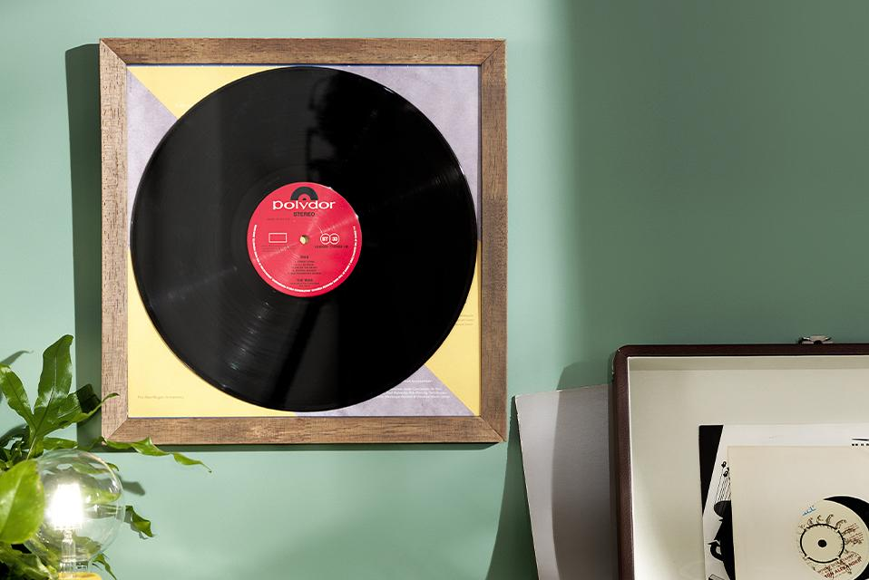 A framed vinyl record on a mint green wall above a record player.