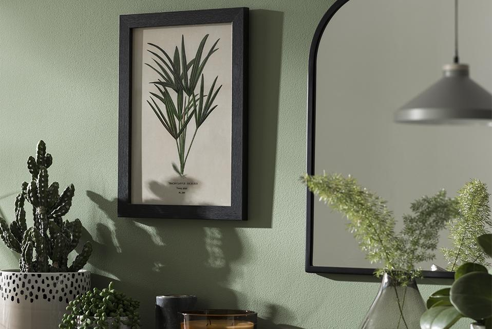 A framed botanical print and mirror on a green wall above potted plants.
