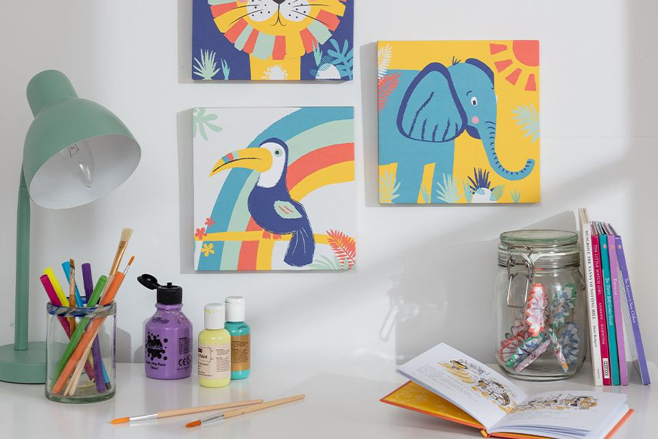 Brightly coloured kids' art prints arranged on a wall above a craft table.