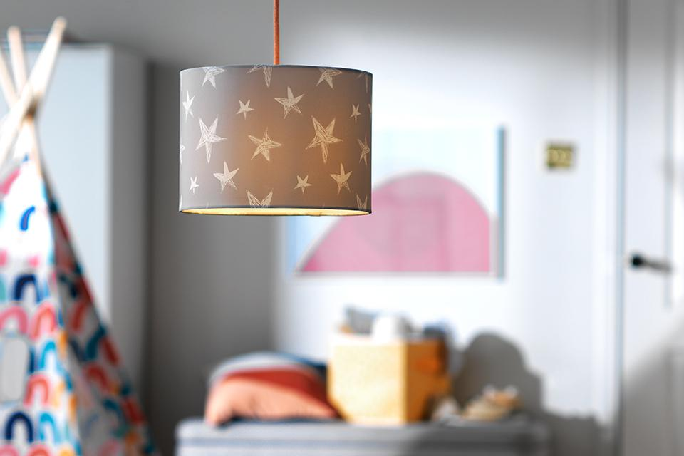 Image of a grey and white star fabric lampshade in a kids' bedroom.
