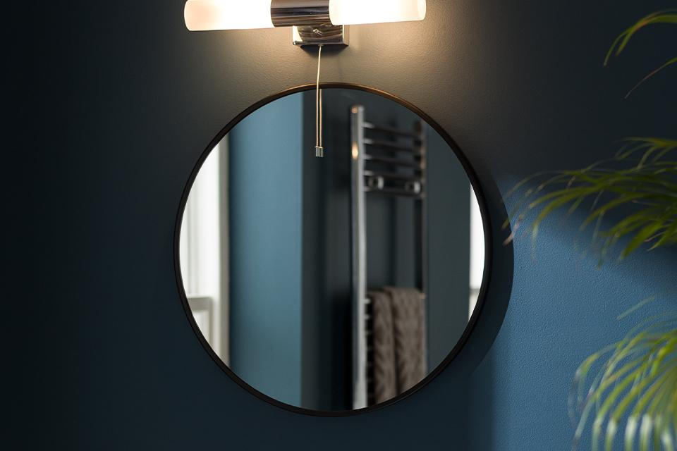 Image of a round, black mirror with a bar light above it.