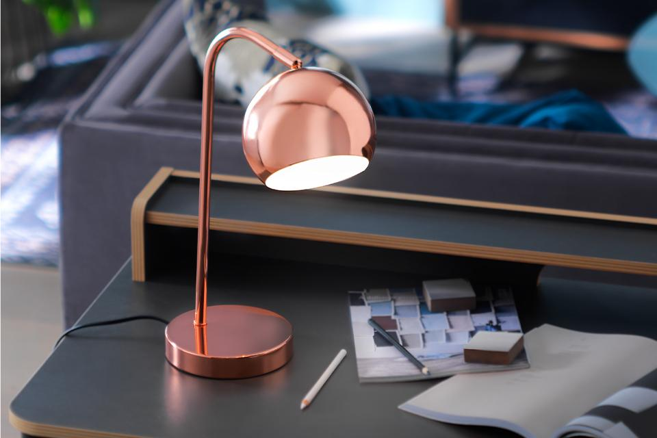 An image of a small, arched table lamp in rose gold.