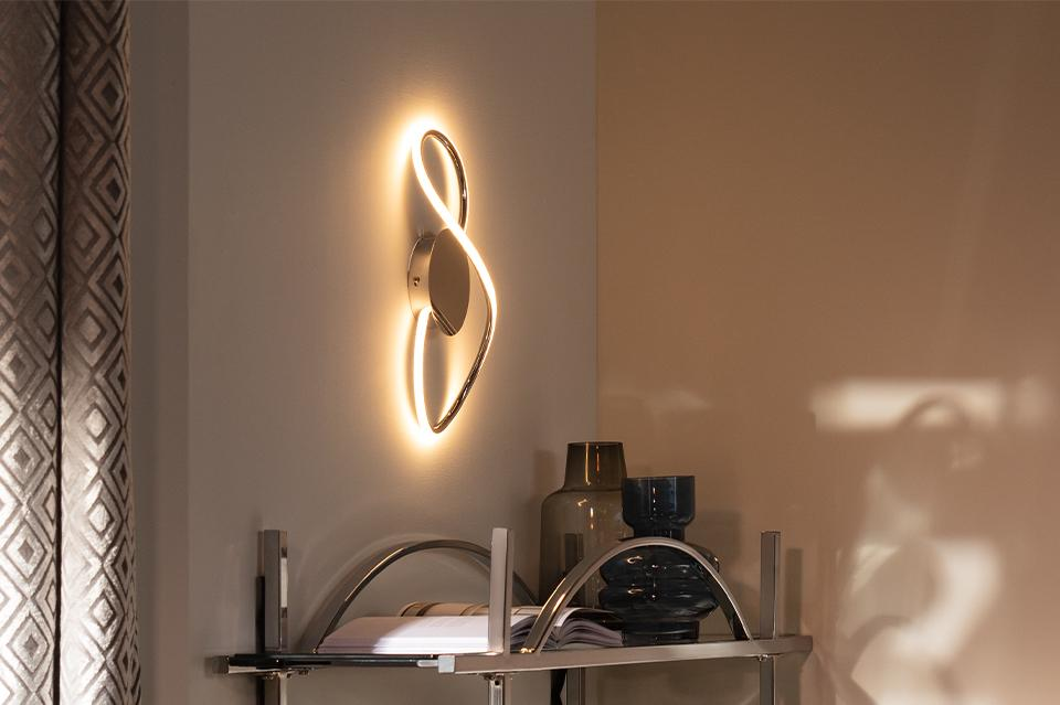 An image of figure 8 shaped wall light above a shelf.