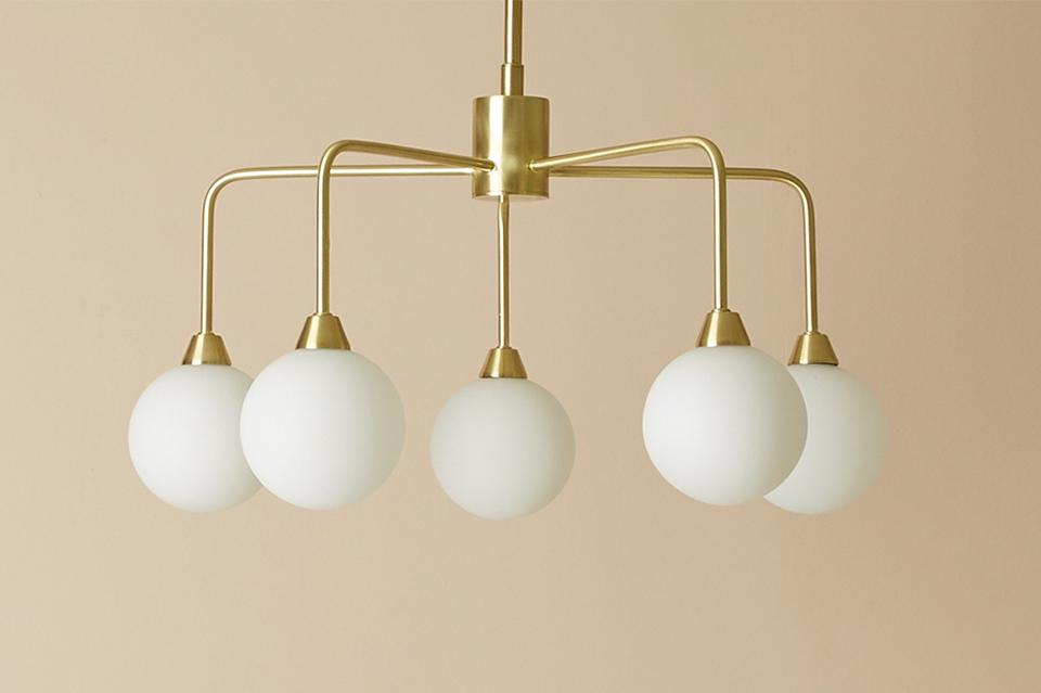 A white and gold claw style ceiling light in a peach coloured room.