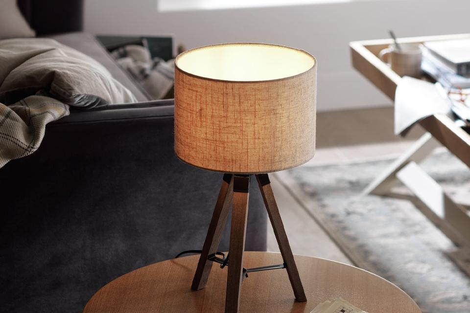 A wooden tripod table lamp with a natural woven shade on a round side table.