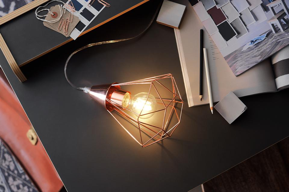 An image of an industrial style table lamp with a copper cage shade.
