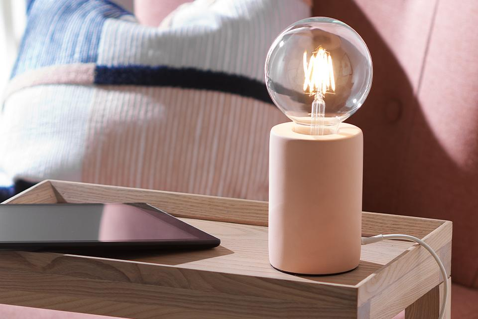 An image of a table lamp with an exposed bulb.