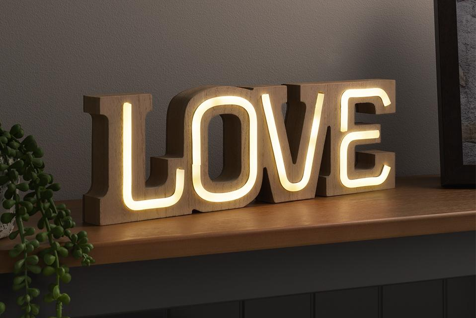 Image of a light-up sign that says 'love'.