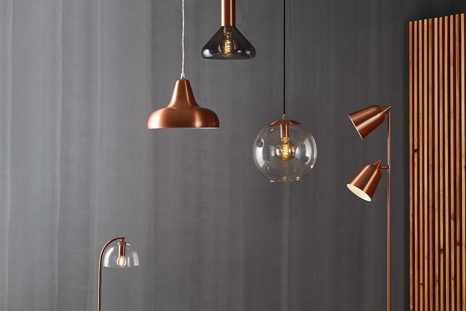 A collection of different copper and glass floor lamps and ceiling lights.