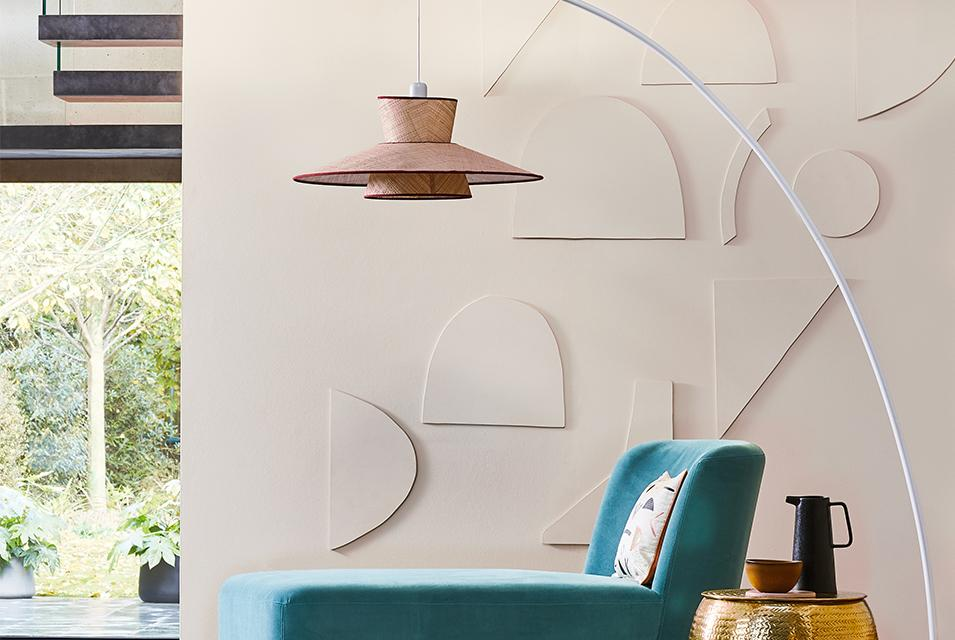 Image of a large arched floor lamp next to a turquoise chaise lounge.