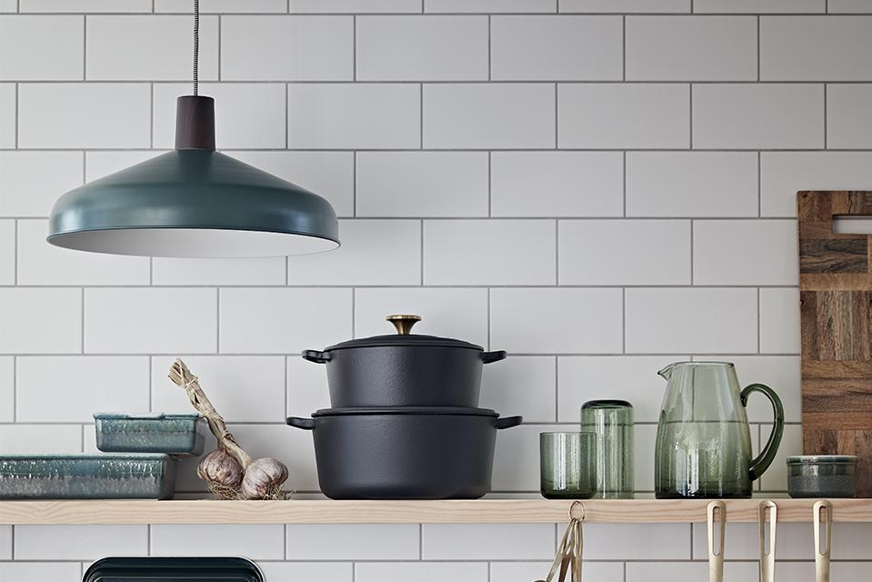 Image of a white, black and turquoise kitchen counter top with a metal pendant light.