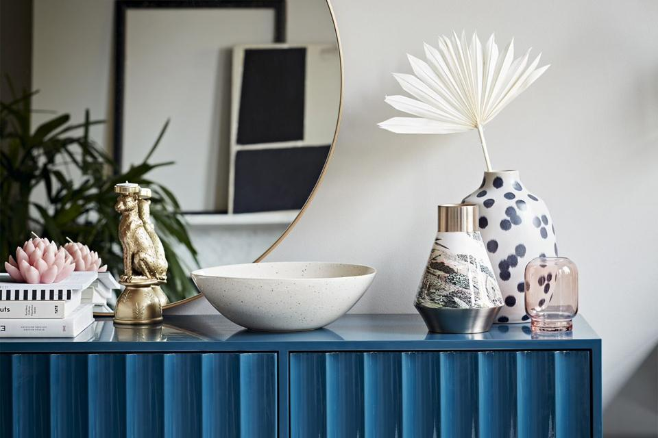 High-gloss petrol blue sideboard with vases and ornaments on top.