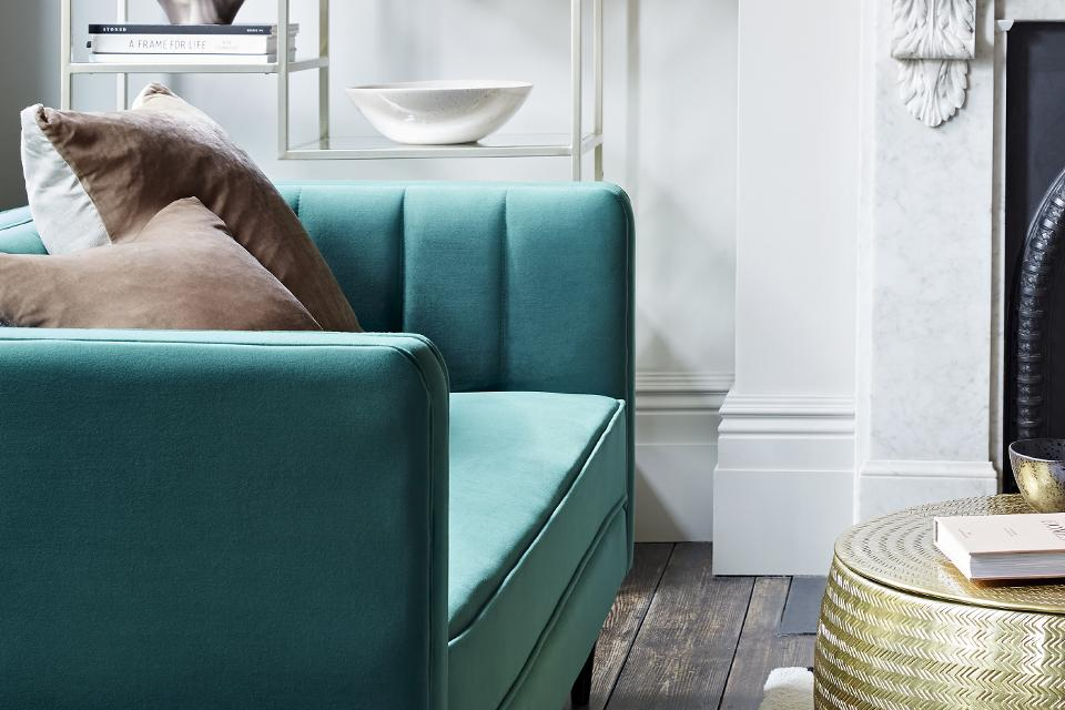 Teal green velvet sofa in a living room with two cushions on top.