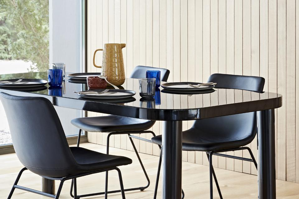 A mid-century style black dining set with brightly coloured tableware.