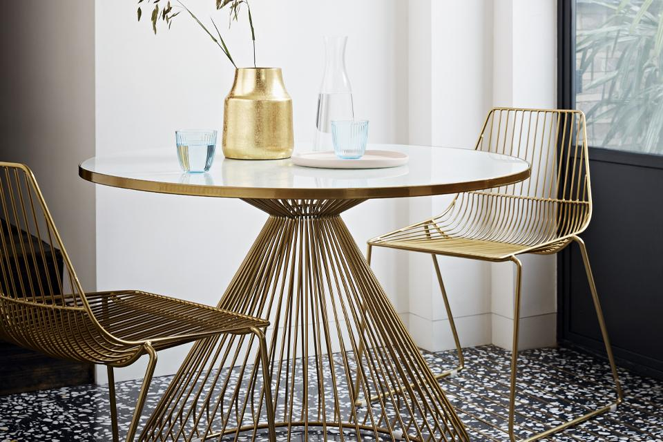 Dining set with brass legs and brass wire chairs.
