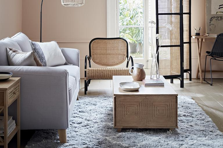 Living room with grey sofa and rattan armchair.
